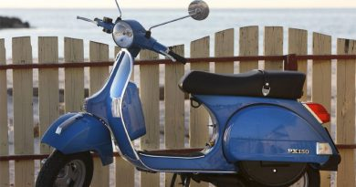 Blue Vespa PX 150 with wooden fence and sea