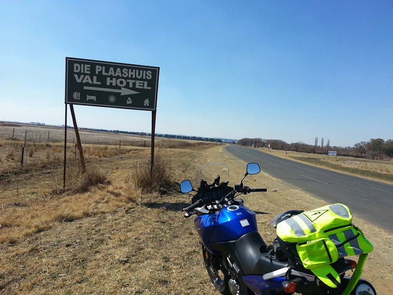 A Suzuki V-Strom and a sign pointing to Val hotel