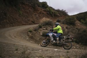 A man in a high-vis rain jacket rounding a corner on his BMW F850GS Adventure