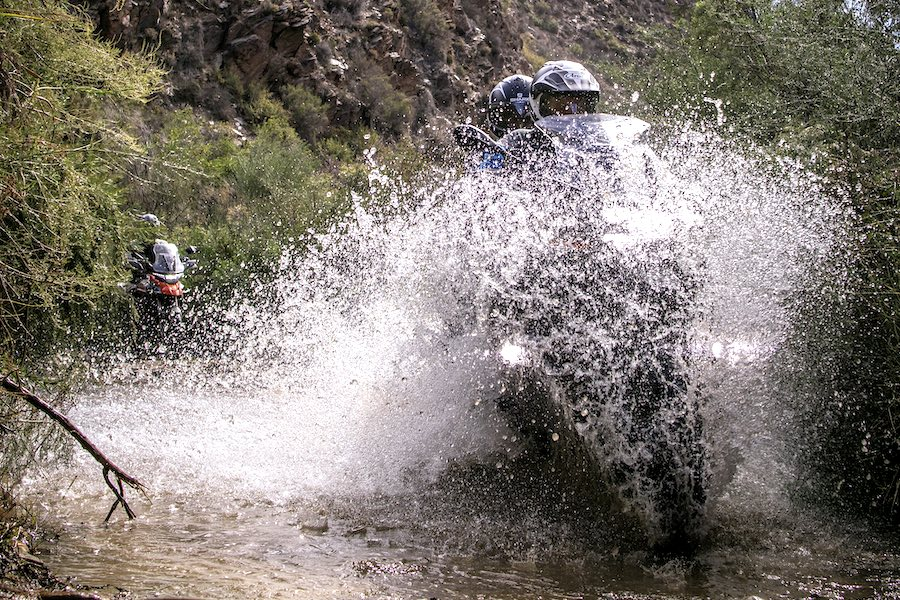 Water splashing up over two motorcyclists on a BMW R1200GS