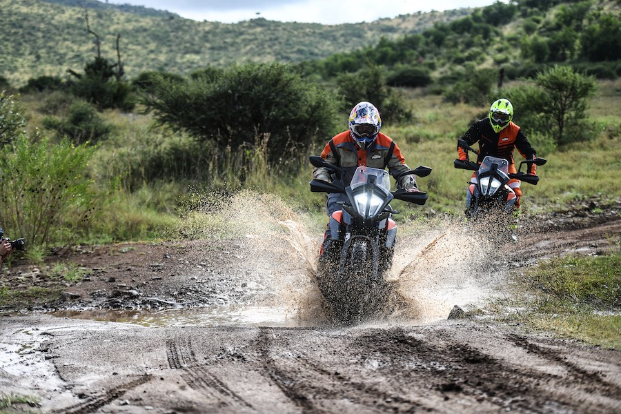 Two bikers riding through muddy waters on KTM 390 Adventures