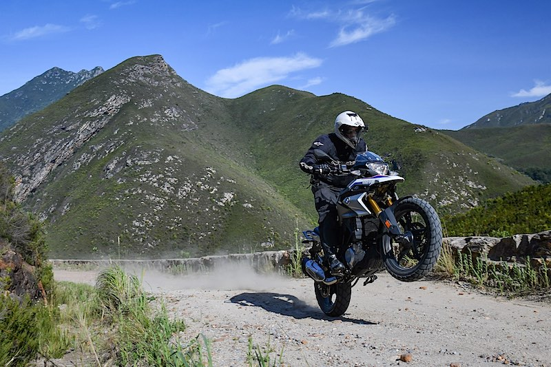 A rider on a BMW 310 GS pops a wheelie