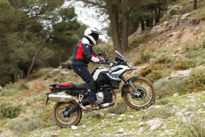 A rider in BMW rider gear, riding up a hill on a BMW F 850 GS