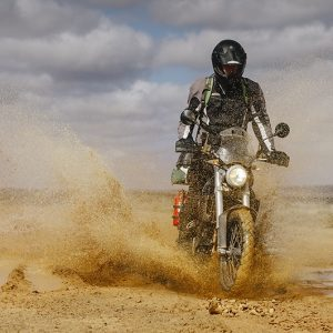 A motorbike rider splashing through muddy water